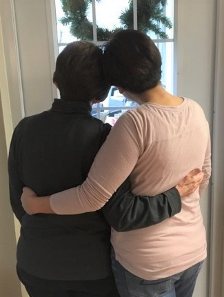 Two women, hugging as they look out a window